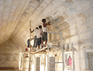Traditional masons cleaning the marble surface